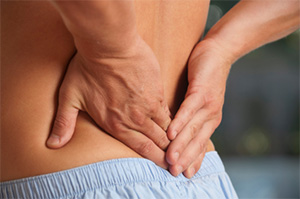 Image of a man holding his lower back in pain